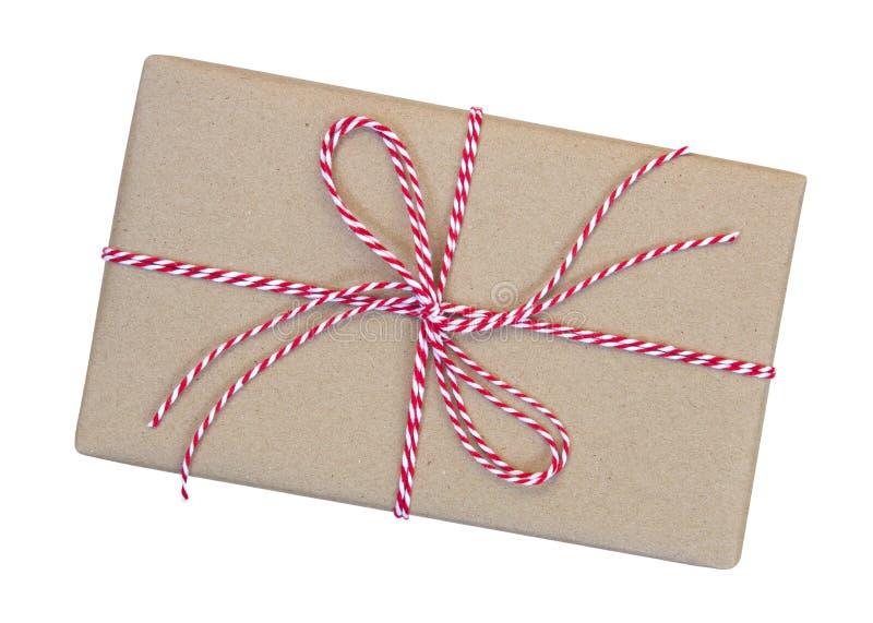 Κιβώτιο δώρων που τυλίγεται στο καφετί ανακυκλωμένο έγγραφο με το κόκκινο και άσπρο σχοινί στοκ εικόνα