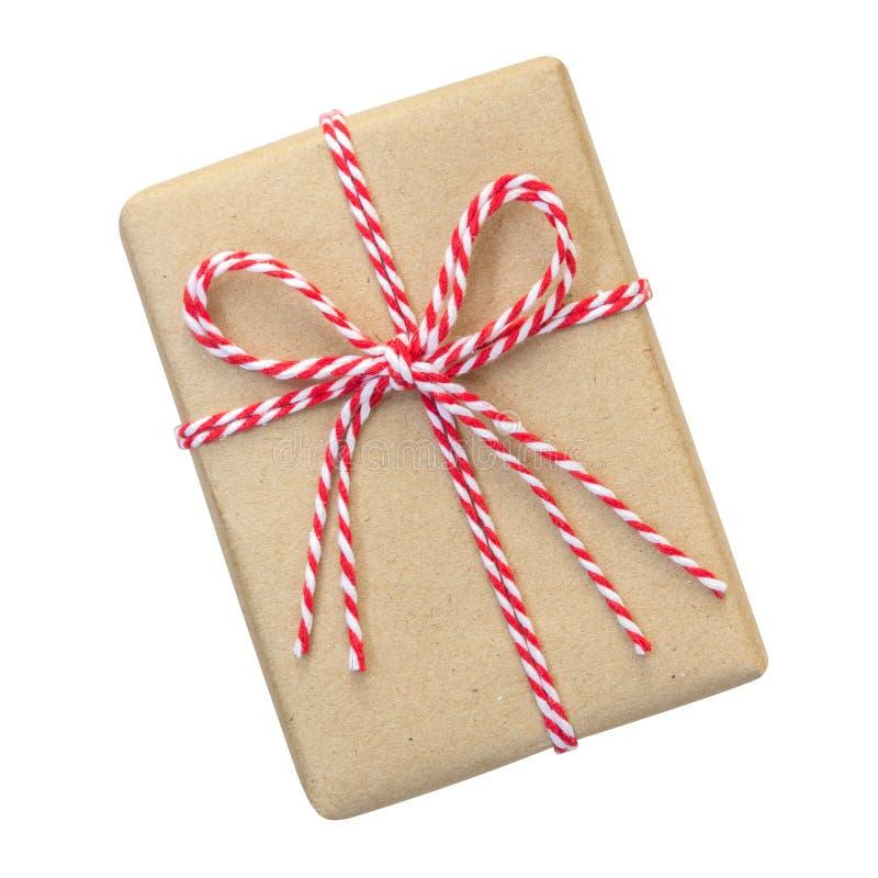 Κιβώτιο δώρων που τυλίγεται στο καφετί ανακυκλωμένο έγγραφο με το κόκκινο και άσπρο σχοινί στοκ εικόνες
