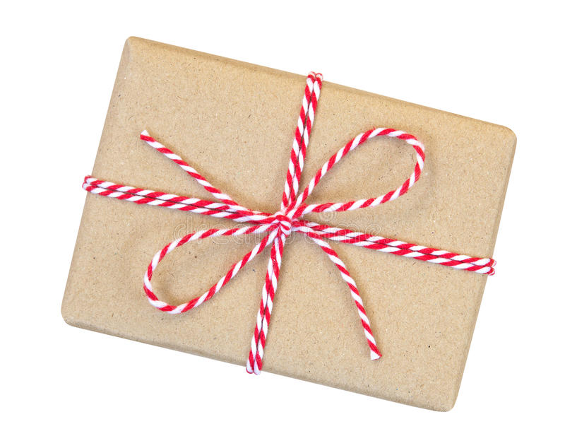 Κιβώτιο δώρων που τυλίγεται στο καφετί ανακυκλωμένο έγγραφο με το κόκκινο και άσπρο σχοινί στοκ φωτογραφία με δικαίωμα ελεύθερης χρήσης