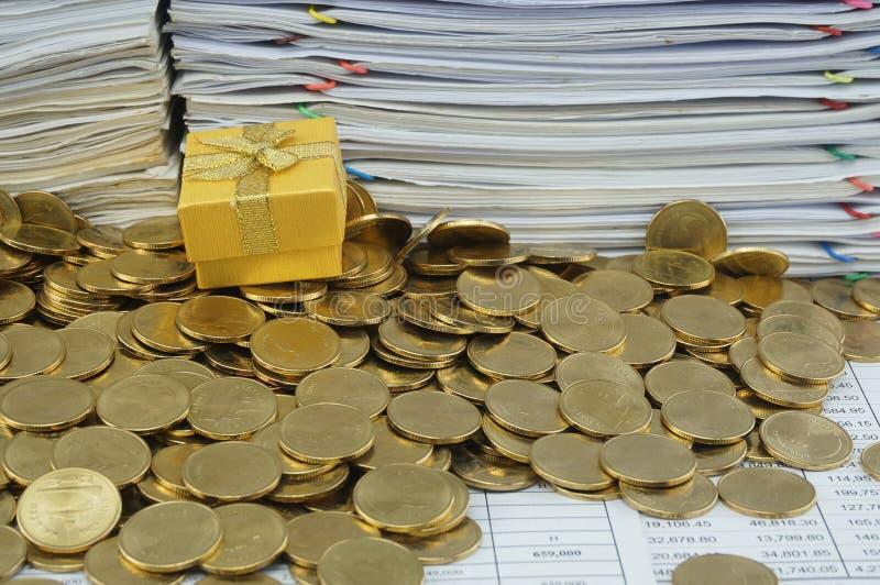 Κιβώτιο δώρων στο σωρό των χρυσών νομισμάτων στοκ εικόνα με δικαίωμα ελεύθερης χρήσης