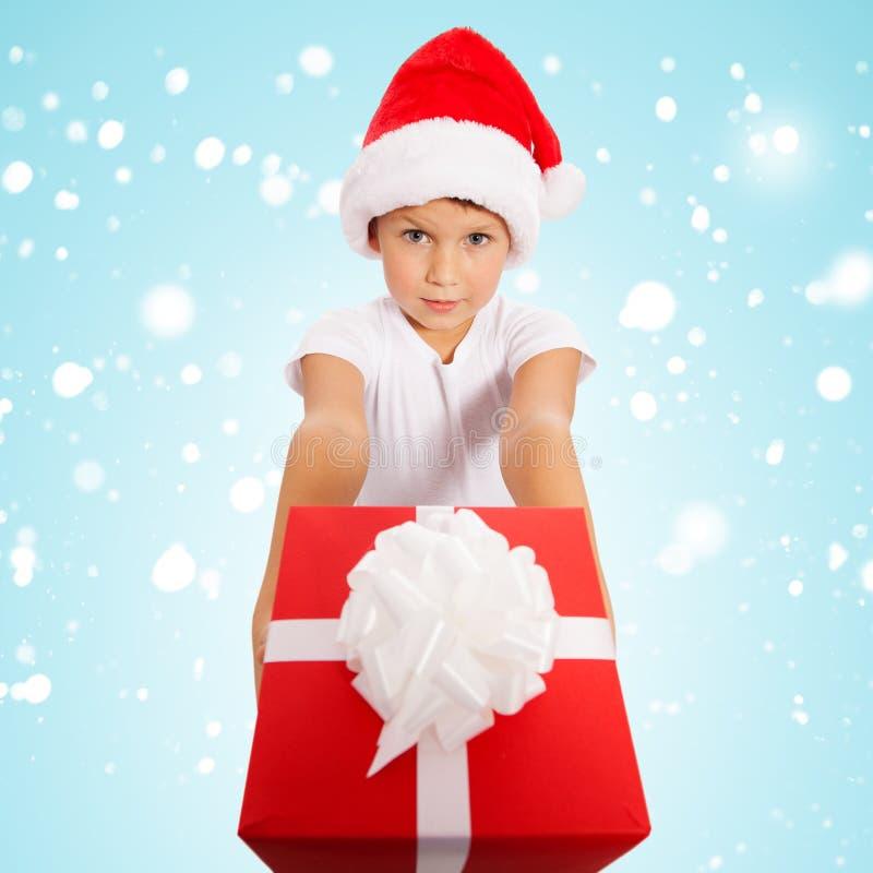 Κιβώτιο δώρων Χριστουγέννων εκμετάλλευσης παιδιών υπό εξέταση στο υπόβαθρο στοκ φωτογραφία