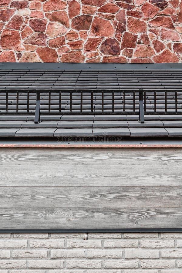 Κιγκλίδωμα στεγών με τις γκρίζες ξύλινες ακτίνες, τα μαύρα κεραμίδια, τον άσπρο τουβλότοιχο και τον κόκκινο encaustic ψαμμίτη στοκ φωτογραφίες