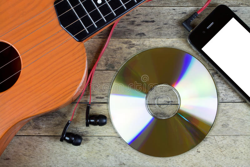 Κιθάρα, δίσκος του CD, έξυπνα τηλέφωνο και ακουστικά στοκ εικόνες με δικαίωμα ελεύθερης χρήσης