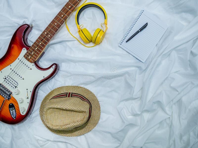 Κιθάρα, ακουστικά, σημειωματάρια, σημειώσεις μουσικής, και καπέλα στην άσπρη τοπ άποψη υφάσματος στοκ εικόνα