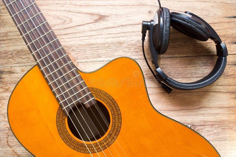 Κιθάρα και ακουστικό στο ξύλινο υπόβαθρο στοκ εικόνα