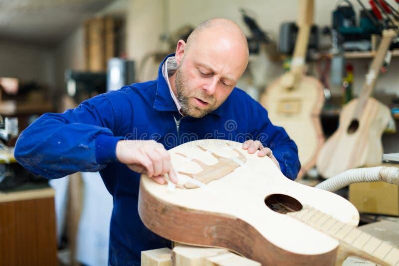 Κιθάρα-κατασκευαστής στο εργαστήριο στοκ εικόνες