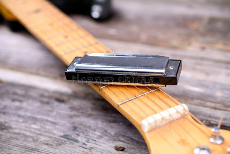 Κιθάρα με τη φυσαρμόνικα μπλε στο ξύλινο έδαφος στοκ φωτογραφίες