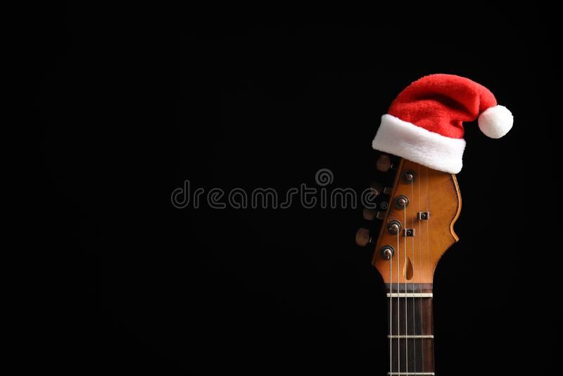 Κιθάρα με το καπέλο Santa στο μαύρο υπόβαθρο στοκ εικόνες