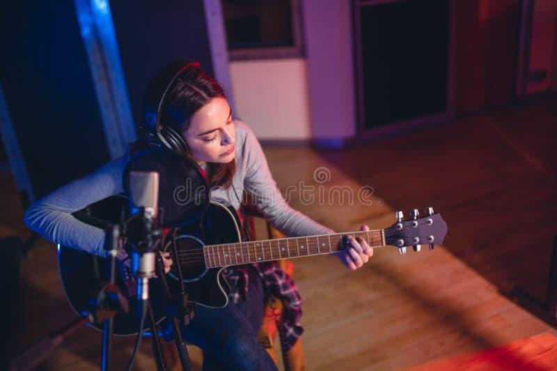 Κιθάρα παιχνιδιού γυναικών σε ένα στούντιο καταγραφής στοκ φωτογραφία με δικαίωμα ελεύθερης χρήσης