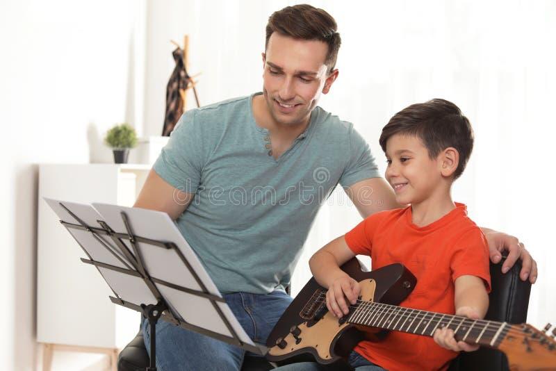 Κιθάρα παιχνιδιού μικρών παιδιών με το δάσκαλό του στο μάθημα μουσικής στοκ εικόνα