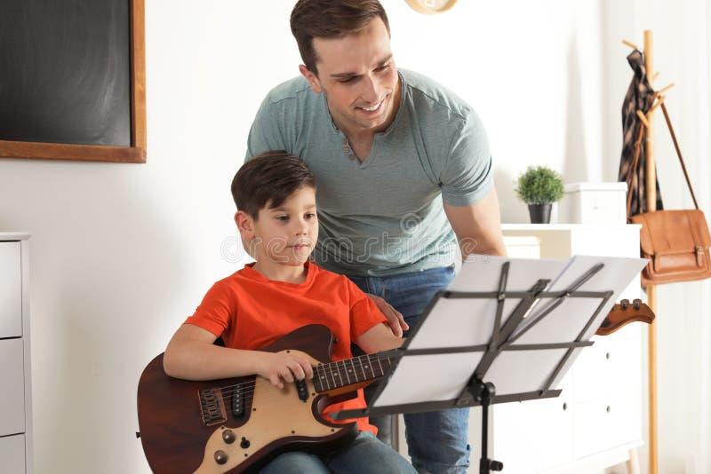 Κιθάρα παιχνιδιού μικρών παιδιών με το δάσκαλό του στο μάθημα μουσικής στοκ φωτογραφία