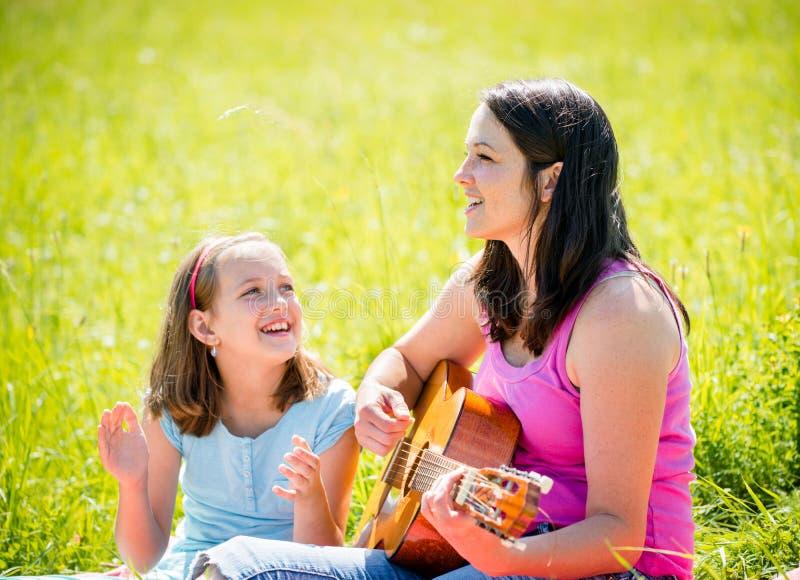 Κιθάρα παιχνιδιού μητέρων στη φύση στοκ εικόνες με δικαίωμα ελεύθερης χρήσης