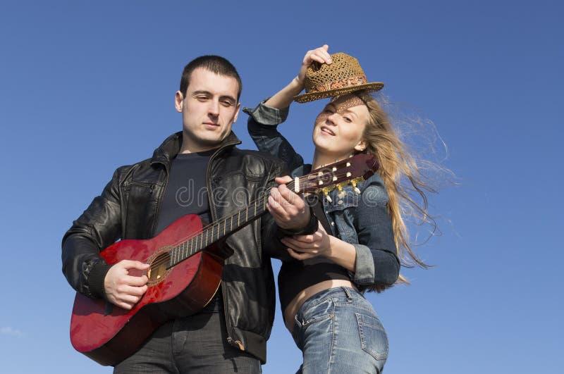 Κιθάρα παιχνιδιού νεαρών άνδρων με τη γυναίκα που χορεύει και βγάζει το καπέλο της στοκ φωτογραφία
