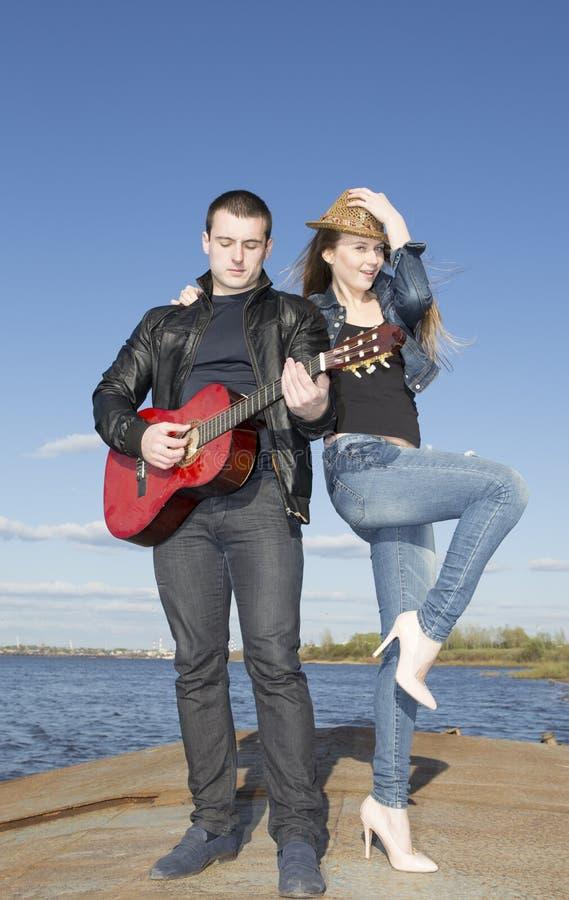 Κιθάρα παιχνιδιού νεαρών άνδρων με τη γυναίκα που χορεύει στοκ εικόνα