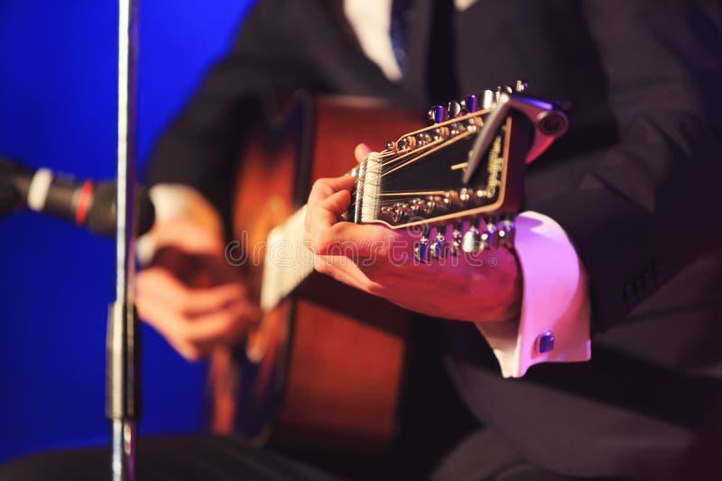 Κιθάρα στα χέρια ενός τραγουδιστή Singer& x27 χέρια του s που παίζουν μια μουσική κιθάρων Άτομο στο κομψό κοστούμι που παίζει μια στοκ φωτογραφίες