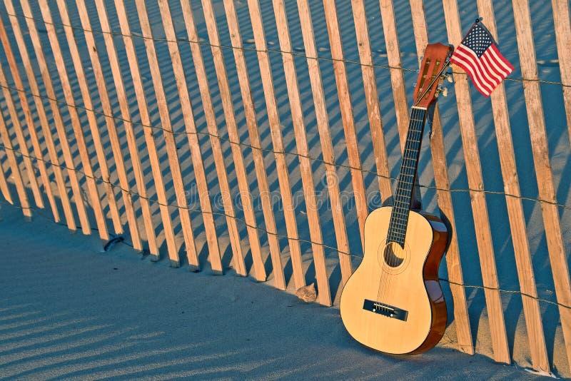 Κιθάρα στο φράκτη παραλιών με τη αμερικανική σημαία στοκ εικόνα με δικαίωμα ελεύθερης χρήσης