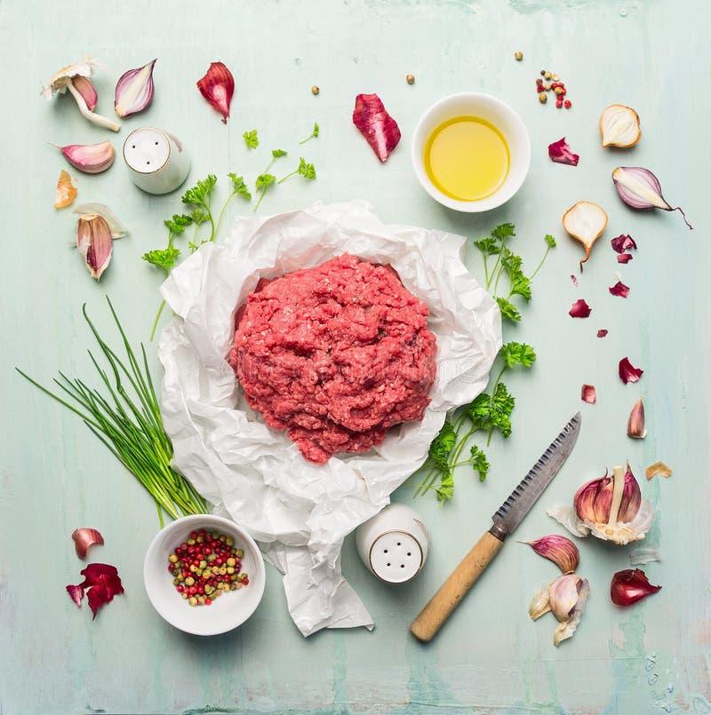 Κιμάς με το μαγείρεμα των συστατικών, του ελαίου, των χορταριών και των καρυκευμάτων στο μπλε ξύλινο υπόβαθρο στοκ φωτογραφία