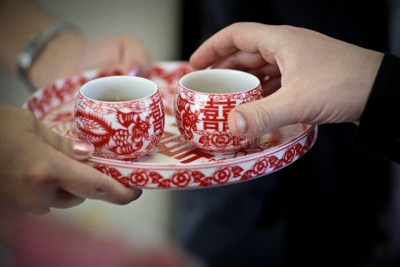Κινεζικά γαμήλιου τσαγιού κύπελλα τσαγιού τελετής παραδοσιακά κόκκινα στον εξυπηρετώντας πατέρα νυφών δίσκων στοκ εικόνες