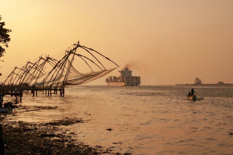 Κινεζικά δίχτυα του ψαρέματος σε Cochi, Κεράλα, Ινδία, με το σκάφος εμπορευματοκιβωτίων στο υπόβαθρο στο ηλιοβασίλεμα στο χρώμα στοκ φωτογραφία με δικαίωμα ελεύθερης χρήσης