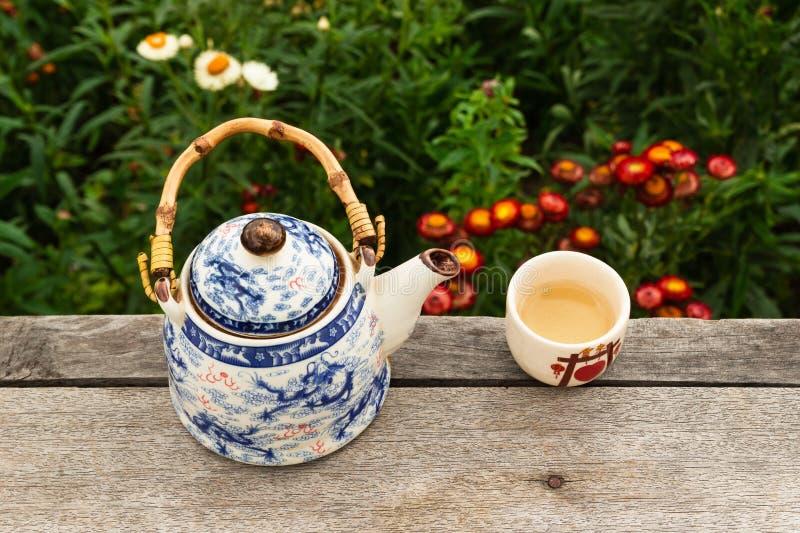Κινεζικά teapot και κύπελλο με το πράσινο τσάι σε έναν ξύλινο πίνακα σε ένα υπόβαθρο των φωτεινών ζωηρόχρωμων λουλουδιών, τοπ άπο στοκ φωτογραφία με δικαίωμα ελεύθερης χρήσης