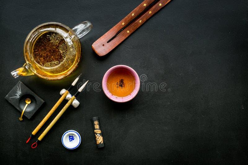 Κινεζικές ή ιαπωνικές παραδόσεις Καλλιγραφία και έννοια τελετής τσαγιού Ειδικός στυλός γραψίματος, μελάνι κοντά teapot και φλυτζά στοκ εικόνες