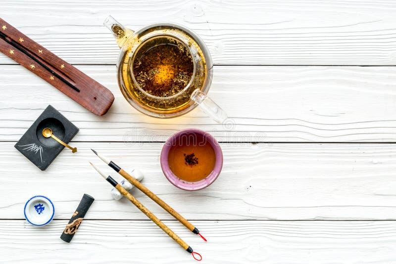 Κινεζικές ή ιαπωνικές παραδόσεις Καλλιγραφία και έννοια τελετής τσαγιού Ειδικός στυλός γραψίματος, μελάνι κοντά teapot και φλυτζά στοκ εικόνες με δικαίωμα ελεύθερης χρήσης