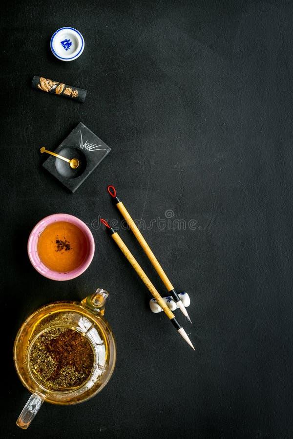 Κινεζικές ή ιαπωνικές παραδόσεις Καλλιγραφία και έννοια τελετής τσαγιού Ειδικός στυλός γραψίματος, μελάνι κοντά teapot και φλυτζά στοκ φωτογραφία
