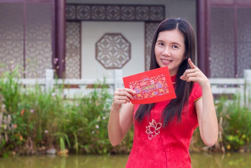 Κινεζική γυναίκα που κρατά το κόκκινο πακέτο ευτυχώς κατά τη διάρκεια της κινεζικής νέας εποχής έτους στοκ εικόνα με δικαίωμα ελεύθερης χρήσης