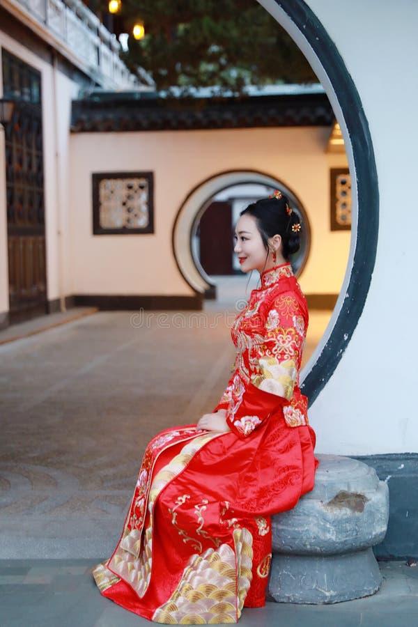 Κινεζική γυναίκα που φορά το κόκκινο φόρεμα μεταξιού της χαρακτηριστικής κινεζικής νύφης, που κάθεται στον κλασσικό κήπο στοκ εικόνες
