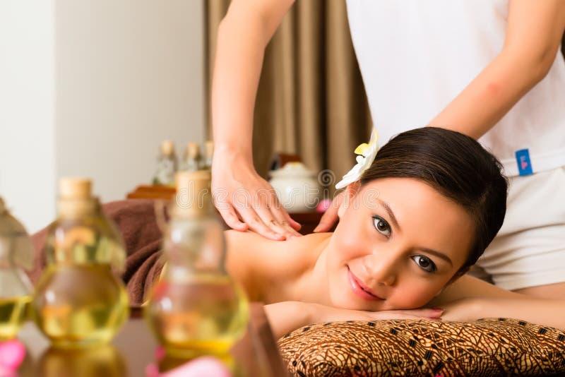 Κινεζική γυναίκα στο μασάζ wellness με τα ουσιαστικά πετρέλαια στοκ φωτογραφία