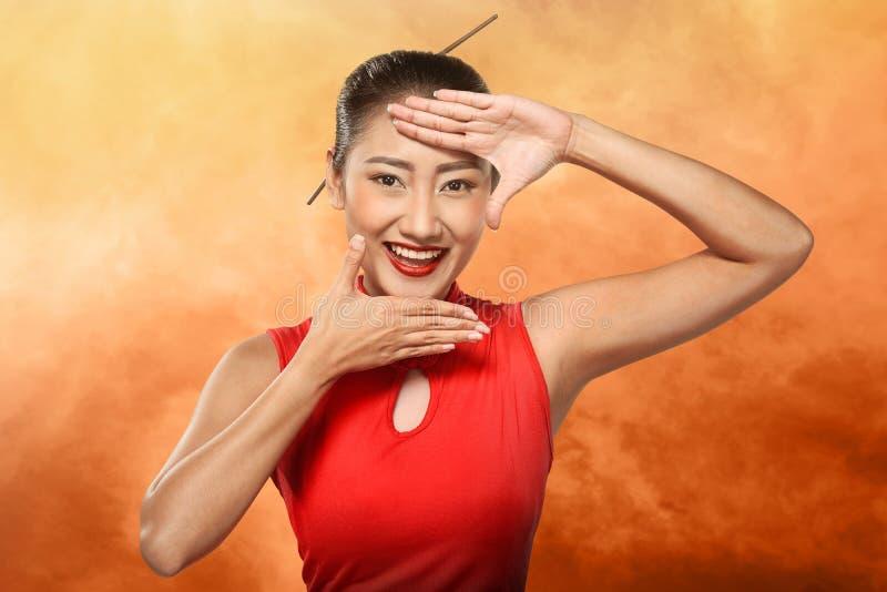 Κινεζική γυναίκα στο φόρεμα cheongsam που πλαισιώνει το πρόσωπό της με το χέρι στοκ εικόνα