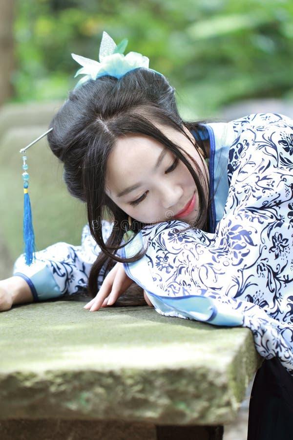 Κινεζική γυναίκα Aisan στο παραδοσιακό μπλε και άσπρο φόρεμα Hanfu, χρόνος θανάτωσης σε έναν διάσημο κήπο στοκ φωτογραφία με δικαίωμα ελεύθερης χρήσης
