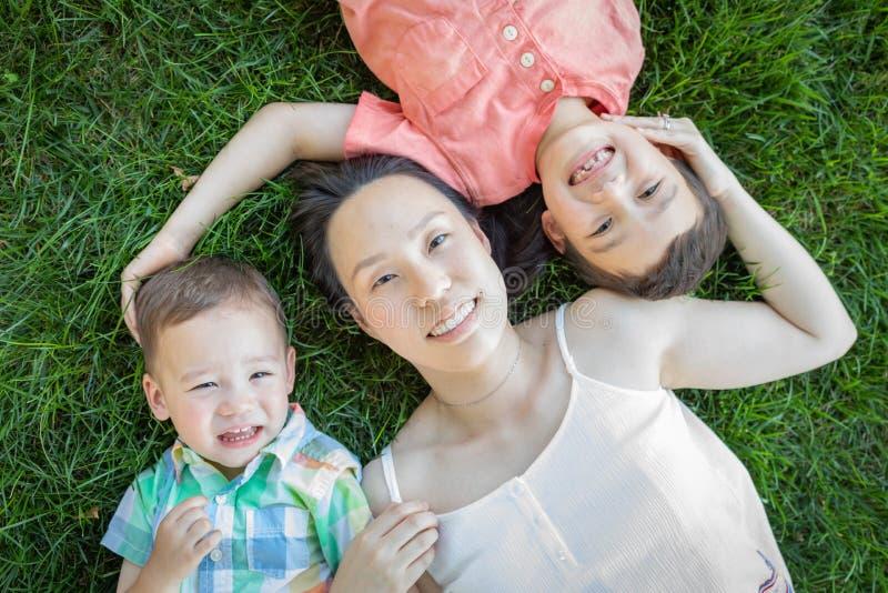 Κινεζική μητέρα και μικτά παιδιά φυλών που βάζουν στη χλόη στοκ εικόνες