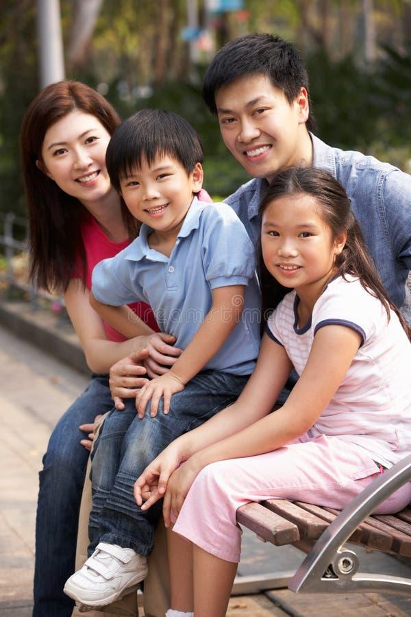 Κινεζική συνεδρίαση οικογενειακού περπατήματος στον πάγκο στο πάρκο στοκ εικόνα