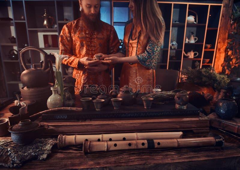 Κινεζική τελετή τσαγιού Το ζεύγος στα ασιατικά παραδοσιακά ενδύματα πίνει το φυσικό τσάι κατά τη διάρκεια μιας κινεζικής τελετής  στοκ φωτογραφίες