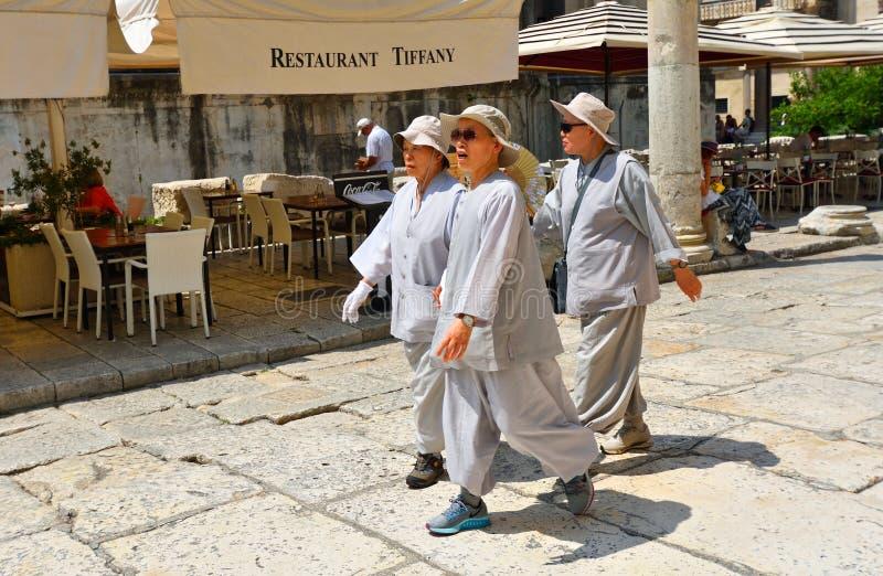 Κινεζικοί γυναικείοι τουρίστες στα κοστούμια προστασίας ήλιων στη διασπασμένη παλαιά πόλη στοκ φωτογραφίες