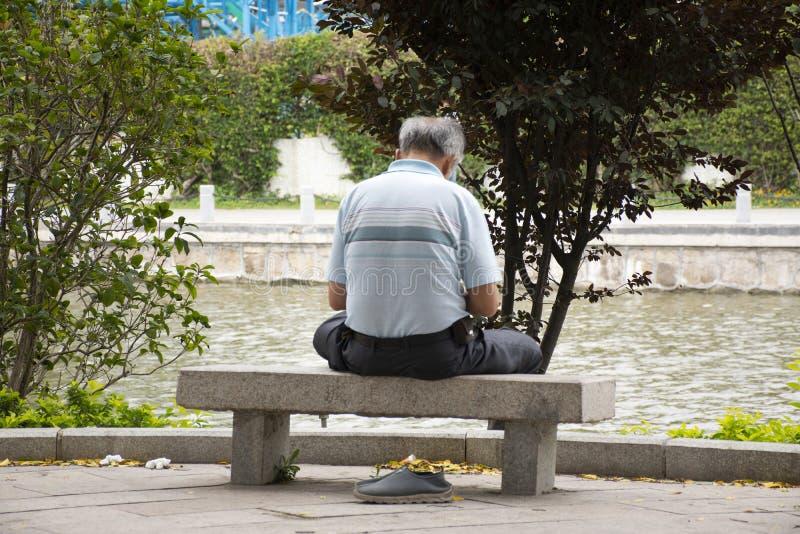 Κινεζικοί ηλικιωμένοι ατόμων που κάθονται μόνο στον πάγκο πετρών και που χαλαρώνουν στο πάρκο Zhongshan στην πόλη Shantou ή Swato στοκ φωτογραφία