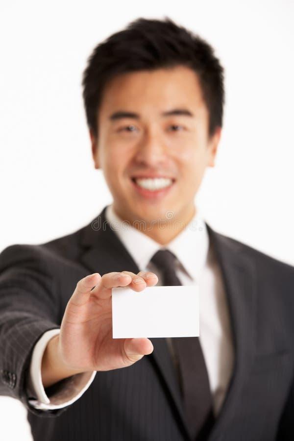 Κινεζικός επιχειρηματίας που προσφέρει τη επαγγελματική κάρτα στοκ εικόνα