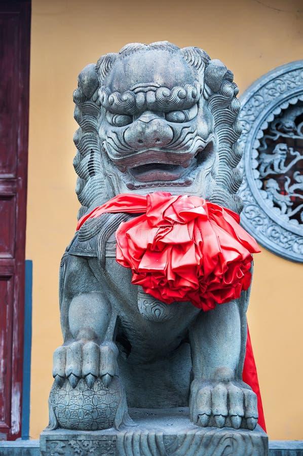 Κινεζικό αυτοκρατορικό άγαλμα λιονταριών, κινεζικά λιοντάρια φυλάκων με το κόκκινο τόξο στο στήθος στοκ εικόνες