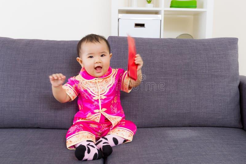 Κινεζικό μωρό που κρατά την κόκκινη τσέπη στοκ εικόνα με δικαίωμα ελεύθερης χρήσης