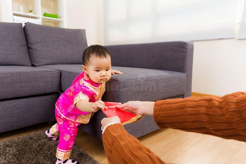 Κινεζικό μωρό που παίρνει την κόκκινη τσέπη από τον ενήλικο στοκ φωτογραφία