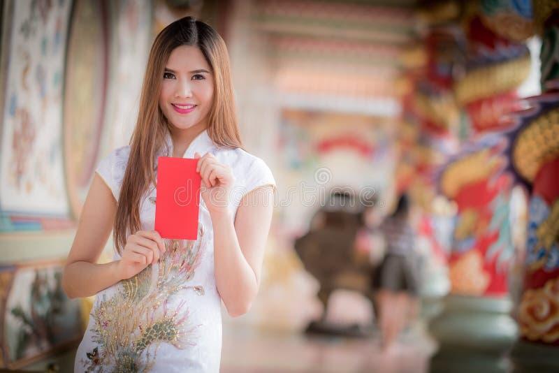 Κινεζικό παραδοσιακό cheongsam φορεμάτων γυναικών και κόκκινος φάκελος λαβής στοκ εικόνες