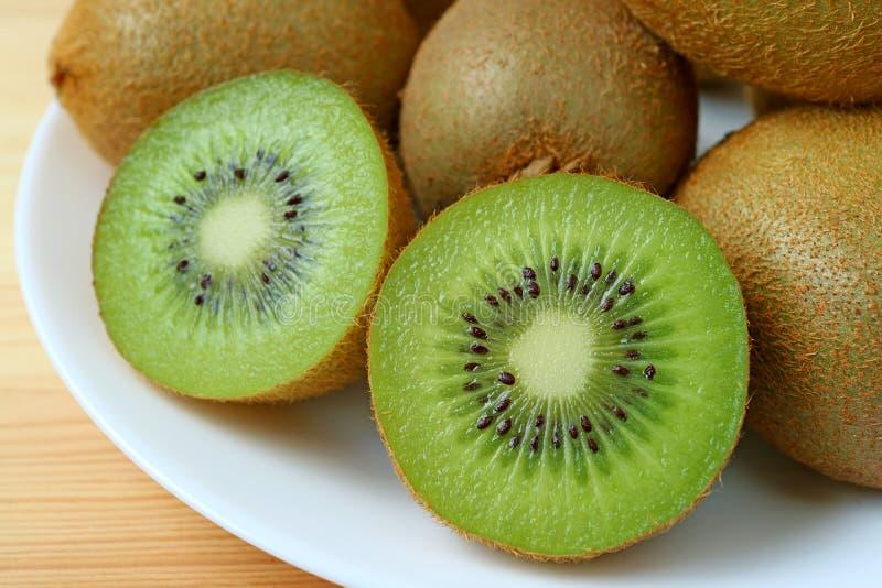 Κινηματογράφηση σε πρώτο πλάνο ένα πιάτο ολόκληρων των φρούτων και διατομές των φρέσκων ώριμων φρούτων ακτινίδιων στοκ εικόνες