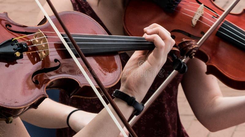 Κινηματογράφηση σε πρώτο πλάνο βιολιών παιχνιδιού γυναικών των χεριών στοκ εικόνες