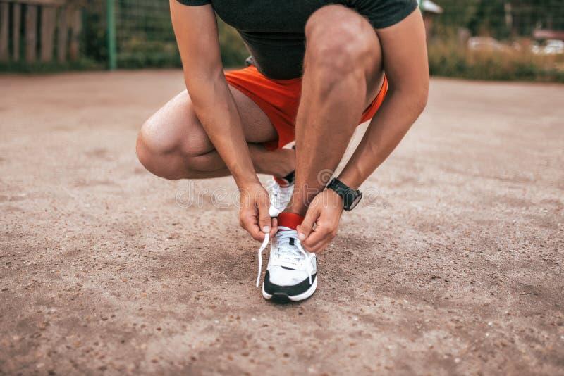 Κινηματογράφηση σε πρώτο πλάνο, δένοντας κορδόνια ατόμων στα πάνινα παπούτσια, ένας αθλητής στην πόλη στην άσφαλτο το καλοκαίρι Ι στοκ εικόνα