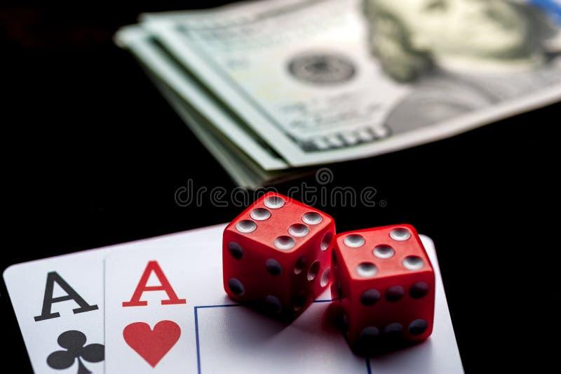 Κινηματογράφηση σε πρώτο πλάνο - δύο άσσοι, οι κάρτες παιχνιδιού και το κόκκινο τυχερό παιχνίδι χωρίζουν σε τετράγωνα στο μαύρο π στοκ φωτογραφίες με δικαίωμα ελεύθερης χρήσης