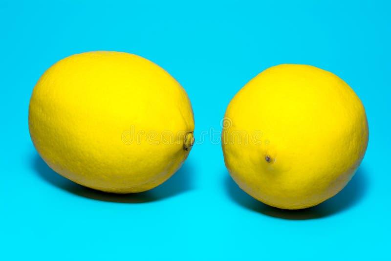 Κινηματογράφηση σε πρώτο πλάνο δύο κίτρινη ώριμη λεμονιών σε ένα μπλε υπόβαθρο, απομόνωση στοκ εικόνα