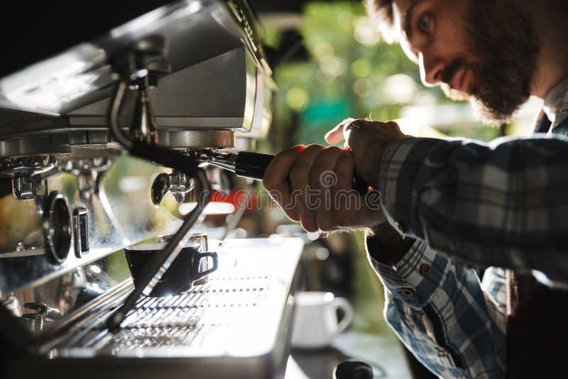 Κινηματογράφηση σε πρώτο πλάνο εικόνας του ευρωπαϊκού ατόμου barista που κατασκευάζει τον καφέ λειτουργώντας στον καφέ ή το καφέ  στοκ εικόνες με δικαίωμα ελεύθερης χρήσης