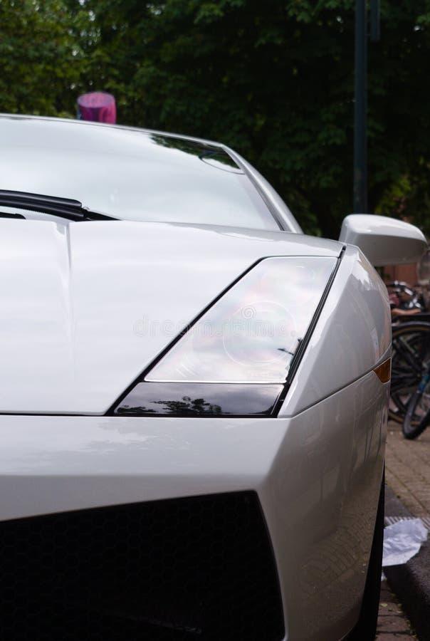 Κινηματογράφηση σε πρώτο πλάνο ενός άσπρου έξοχου αυτοκινήτου που σταθμεύουν στην οδό στοκ φωτογραφίες