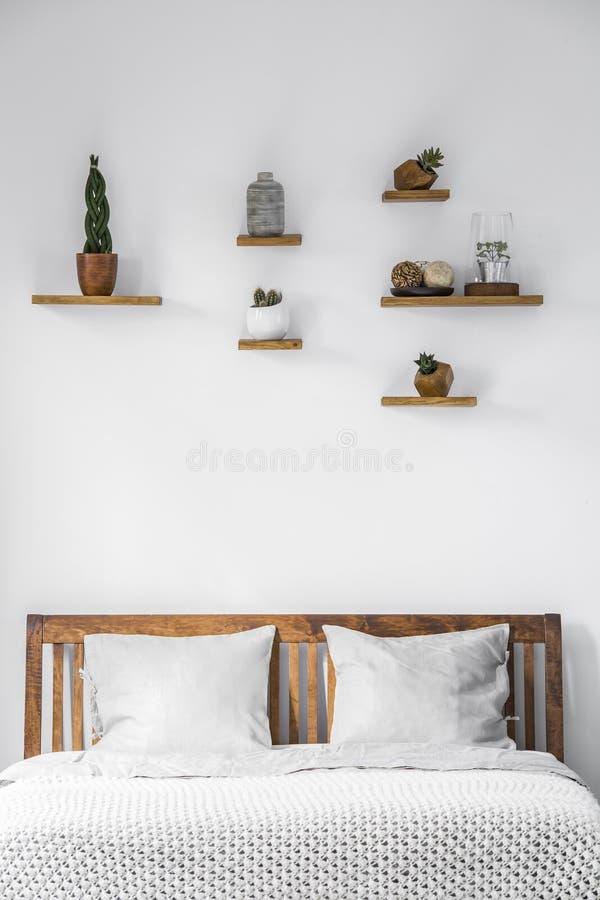 Κινηματογράφηση σε πρώτο πλάνο ενός άσπρου τοίχου με τις μικρές διακοσμήσεις στα ράφια ανωτέρω στοκ εικόνες με δικαίωμα ελεύθερης χρήσης